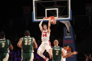 Wisconsin's Frank Kaminsky hits a reverse dunk as UAB's Chris Cokley (3), Lewis Sullivan (35) and Nick Norton (2) run in during their game in the Battle 4 Atlantis basketball tournament in Paradise Island, Bahamas, Wednesday Nov. 26, 2014. (AP Photo/Tim Aylen)