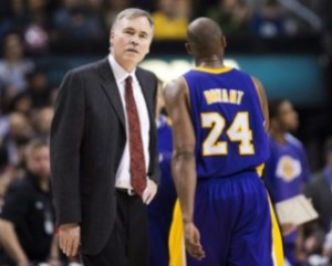 Los Angeles Lakers head coach Mike D'Antoni, left, looks on as guard Kobe Bryant (24) walks by on a timeout while playing against the Toronto Raptors during the second half of an NBA basketball game, Sunday, Jan. 20, 2013, in Toronto. The Raptors won 108-103. (AP Photo/The Canadian Press, Nathan Denette)