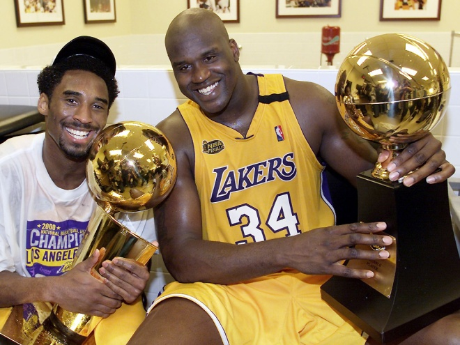 LOS ANGELES, UNITED STATES: Kobe Bryant (L) of the Los Angeles Lakers holds the Larry O'Brian trophy as teammate Shaquille O'Neal (L) hold the MVP trophy after winning the NBA Championship against Indiana Pacers 19 June, 2000, after game six of the NBA Finals at Staples Center in Los Angeles, CA. The Lakers won the game 116-111 to take the NBA title 4-2 in the best-of-seven series. (ELECTRONIC IMAGE) AFP PHOTO (Photo credit should read AFP/AFP/Getty Images)